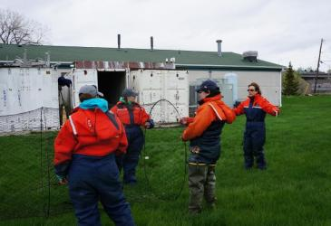 Three students in orange float suits hold a conical trap net open, while a fourth person gestures behind them, during an on-land demonstration. There is a white building in the background.