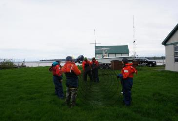 Students in orange float suits hold a conical trap net open, while Dr. Alicia Pérez-Fuentetaja describes how it functions, during an on-land demonstration. The picture is taken from front-on, looking toward the opening of the net.