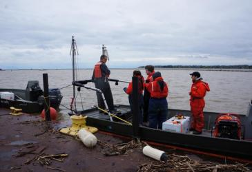 Mark Clapsadl (left) gets ready to launch the electrofishing boat. He is explaining to the students how they will collect fish while electrofishing.
