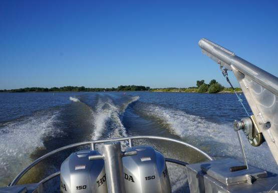 The back of a boat with two engines and a davit. The boat is throwing wake as it goes.