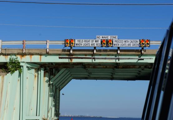 "A bridge with signals and signs saying ""no wake zone"" and explaining how to proceed"