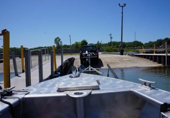 The nose of a boat near a dock. A truck with a trailer is slightly ahead of the boat near the edge of the water.