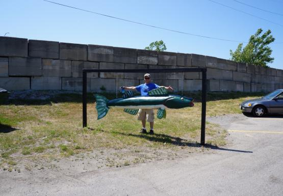 A person stands by a sign in the shape of a large green fish