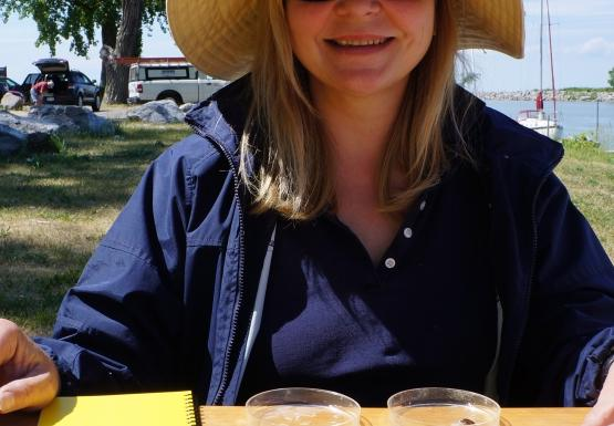 A person in a hat and sunglasses sits at a picnic table with petri dishes and small bottles.