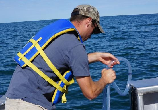 A person lowers a tube over the side of a boat