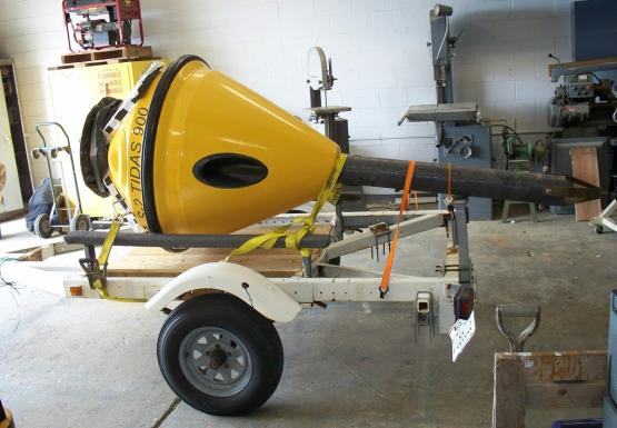 The yellow body of a buoy sits on a trailer in a garage