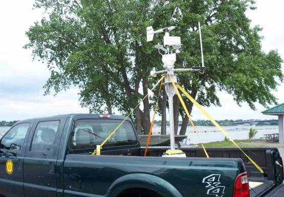 A mast with meteorological equipment stands up in the back of a pickup truck