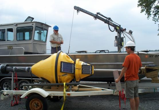 A person wearing a hard hat operates a small crane on the deck of a boat that's on land. Another supervises as the crane lifts a yellow buoy off of a trailer.