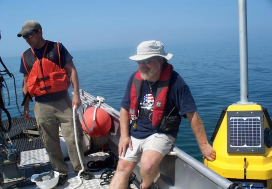 A person sits on the edge of a boat. A yellow buoy sits in the water next to them. Another person on the boat holds a rope.