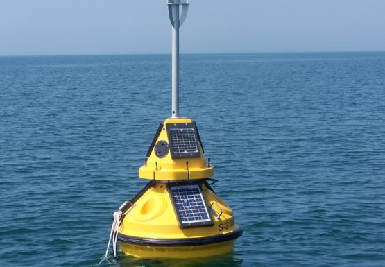 A yellow buoy with meteorological instruments and solar panels sitting in the water