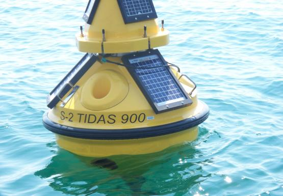 "A yellow buoy with solar panels sits in the water, labeled ""S-2 Tidas 900"""
