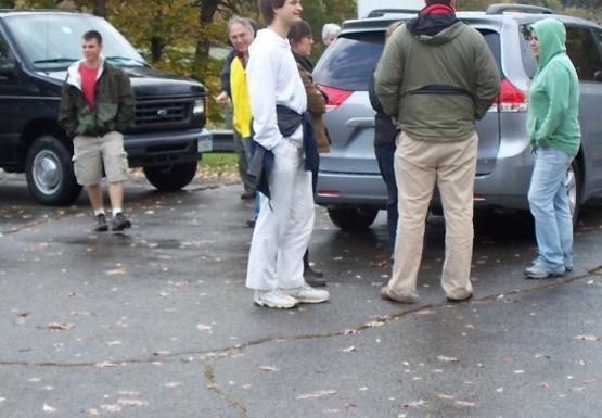 A group of people standing in a parking lot near some cars. A van is hooked up to a boat.