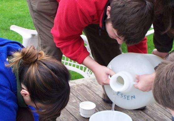 A group of people work together to pour a jug of water into a funnel over a sieve.