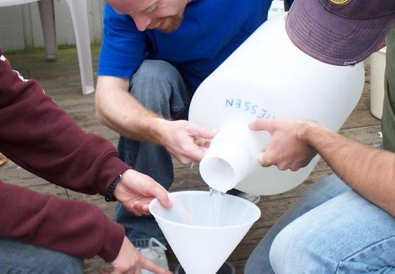 A different group of people work together to pour a jug of water into a funnel over a sieve.