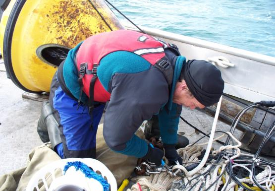 A person uses pliers to unhook two pieces of rope on the deck of a boat. There is rope and chain on the deck, and a buoy is lying on the deck.
