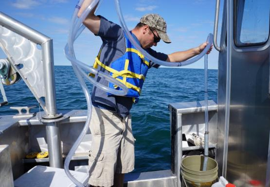 A person on a boat empties a long tube into a bucket