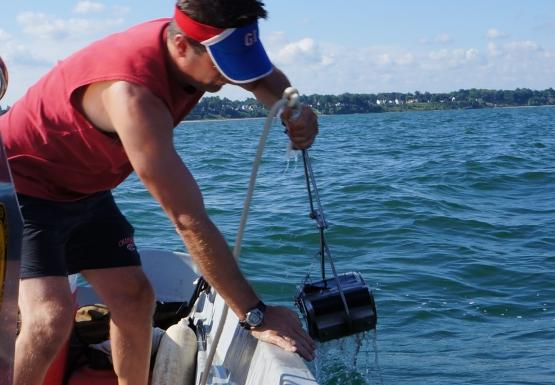 A person pulls a metal device attached to a rope over the side of a boat