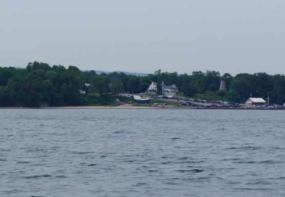 A parking lot with many cars by the water. There is a large house, a short stone light house, and a wooden ship on land nearby.