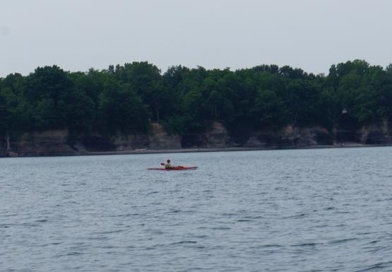 A person in a kayak paddles in front of a short cliff that is unevenly erroded