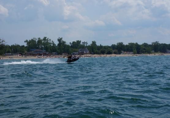 A person rides a jet ski by a beach full of people. There are a few small boats anchored near the beach.