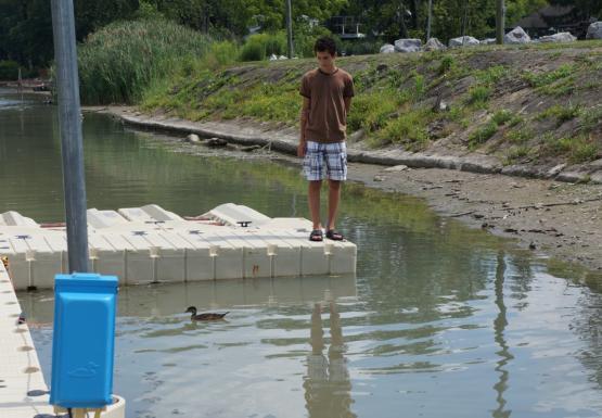 An adolescent stands at the end of a dock near shore. There's a duck in the water in front of them.