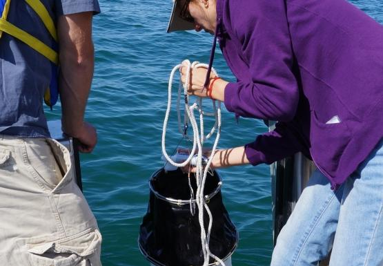 A person holds a conical net over the side of a boat while a second person watches. The first person is checking something in the mouth of the net.
