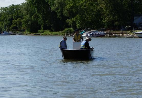Three people sit on a boat on the water