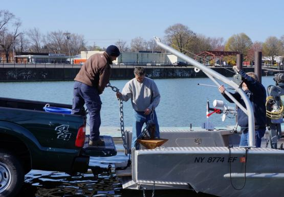 A person hands an anchor on a chain from the back of a pickup truck across to someone standing in the bow of a boat.