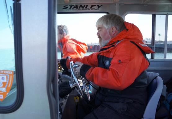 A person in an orange and blue float suit sitting at the helm of a boat