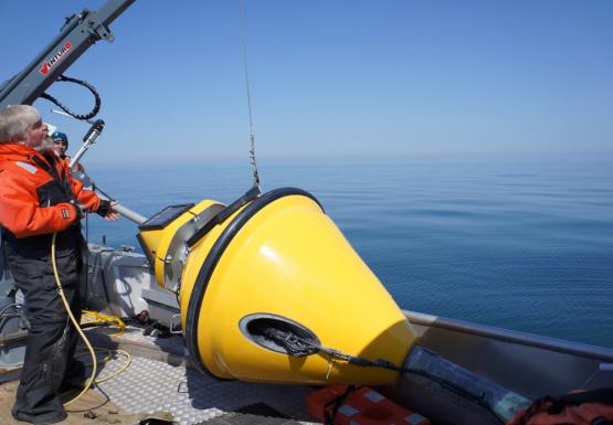 A yellow buoy sits on the deck of a boat. A cable goes from a handle to a small crane. A person stands by the side near the controls of the crane.