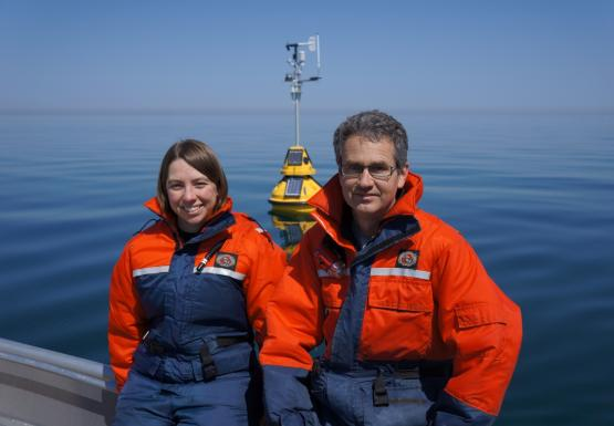 Two people in orange and blue float suits sit in on a boat in front of a buoy in the water.