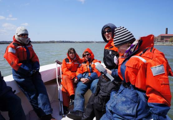 Students sitting in the front of the boat. One holds a grey instrument. One of the students has crutches.