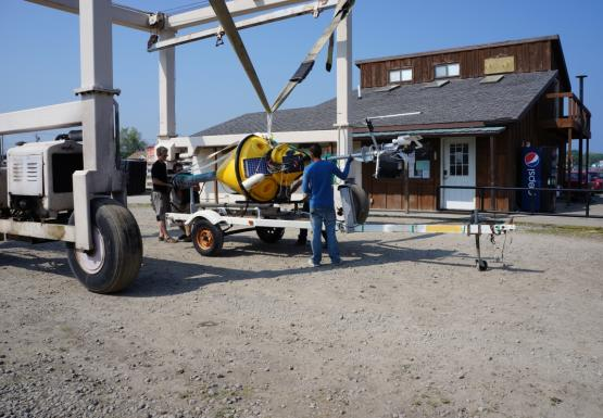 A strap on a large metal frame begins to lift a buoy that's lying on a trailer.
