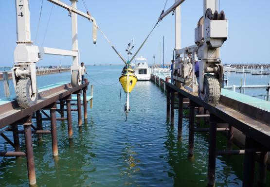 A buoy hangs over the water from a strap on a large metal frame.