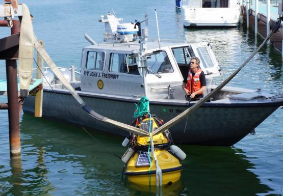 "A person stands in the front of a boat called ""R/V John J. Freidhoff,"" near a buoy in the water at the end of a boat slip. There are straps from the buoy to a metal frame."