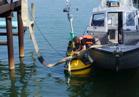 A person on a boat leans over the side to remove a large strap from a buoy.