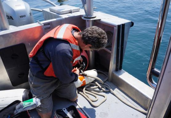 A person in a life jacket kneels on the deck of a boat and uses tools to attach two ropes together.