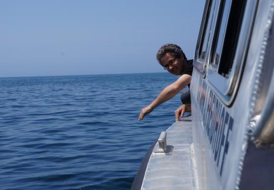 A person leans over the side of a boat. Their arm is extended as if they just threw something.