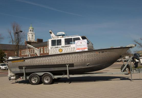 a silver boat sits on a trailer in front of an academic building with a placard for the 50th anniversary of the Great Lakes Center