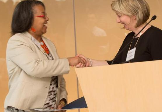 two women shake hands at a podium