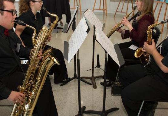 four people playing saxophone sit facing each other with music stands. There are posters on easels and people in the background.