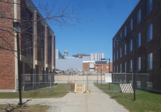 View of a construction site between two buildings. A chain-link fence is up between the buildings, and it is propped in place on either side with pallets.