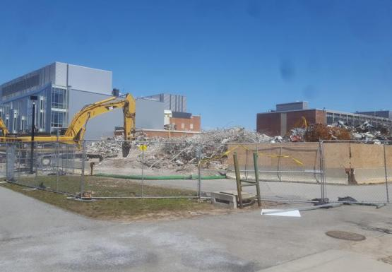 A field of debris next to a grey building and a brick building. The construction area is surrounded by chain-link fencing. Two excavators are parked in the construction zone.