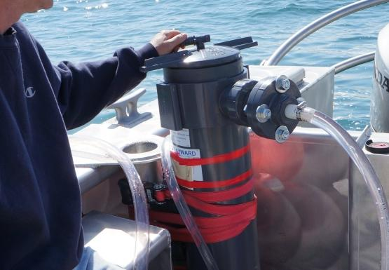 A person sits on a boat next to a grey cylinder with tubes running out of it