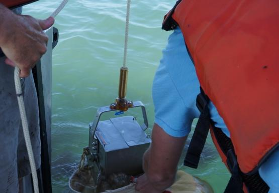 One person holds a rope with a metal box device over the edge of a boat, while a second person puts a net under it at the water level.