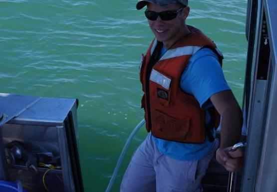 A person in the back of a boat holds a tube in the water