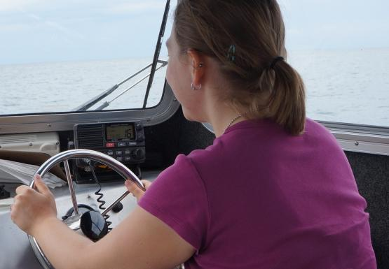 A person sits inside the cabin of a boat at the steering wheel