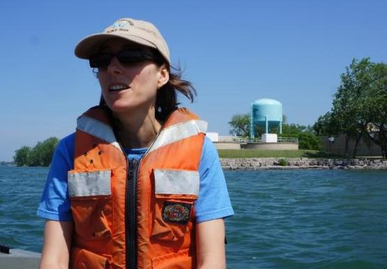 A person wearing a hat and a life jacket sits in a boat. There is a building and a water tower behind them.