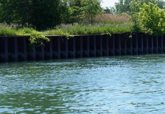 A metal wall along the edge of the water.