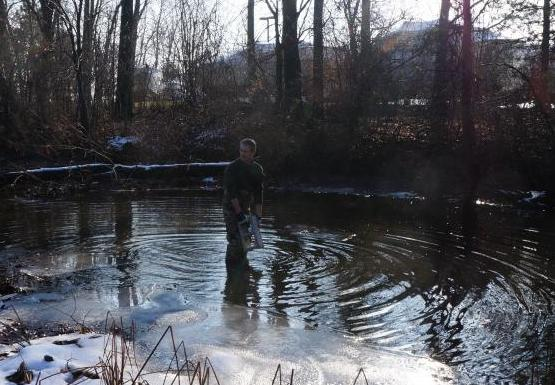 A person standing in the shallow water of an icy creek lowers a cinderblock into the water.